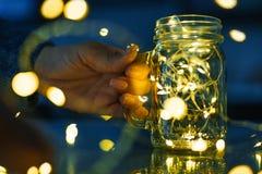 Женские руки держа стеклянную кружку с гирляндами светов Стоковые Изображения RF