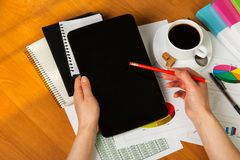 Женские руки держа таблетку и карандаш, тетради, учет, a Стоковое Фото