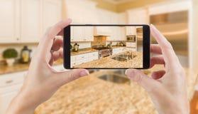 Женские руки держа умный телефон показывая фото кухни Beh Стоковая Фотография RF
