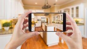 Женские руки держа умный телефон показывая фото кухни Beh Стоковая Фотография