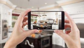 Женские руки держа умный телефон показывая фото кухни Beh Стоковые Фото
