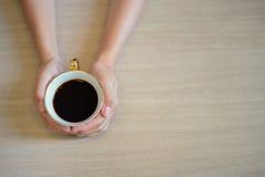 Женские руки держа чашку кофе с кофе эспрессо на деревянном столе Стоковая Фотография RF