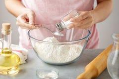 Женские руки добавляют соль в стеклянный шар с мукой стоковое фото