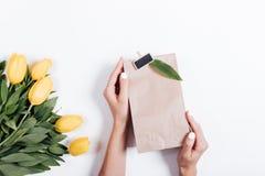Женские руки держа бумажную сумку с подарком около букета  Стоковая Фотография