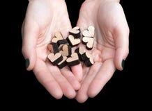 Женские руки держа деревянные сердца Стоковые Фото
