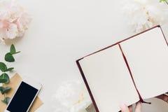 Женские руки держа пустую тетрадь на предпосылке цветков и телефона Взгляд сверху Насмешка вверх Стоковая Фотография RF