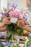 Женские руки держа пустые визитную карточку и букет красивых цветков Стоковая Фотография RF