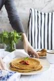 Женские руки держа плиту с crepes Стоковая Фотография