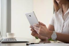 Женские руки держа цифровую таблетку на столе работы, конце вверх Стоковое Изображение