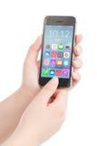 Женские руки держа черный умный телефон с красочным применением стоковое фото rf