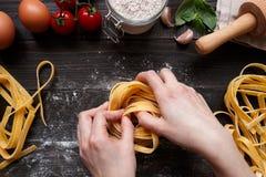 Женские руки делая свежие домодельные макаронные изделия Ингридиенты макаронных изделий на темном взгляд сверху деревянного стола Стоковое Фото