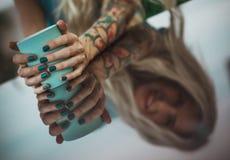 Женские руки закрывают вверх по держать кружку бирюзы Отражение на таблице обедающ на открытом воздухе, современные пить девушки Стоковая Фотография