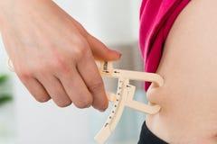Женские руки измеряя тучный живот Стоковое фото RF