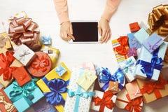 Женские руки используя компьтер-книжку цветастые подарки стоковые фото