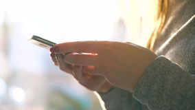 Женские руки используя смартфон против запачканного городского пейзажа в заходящем солнце