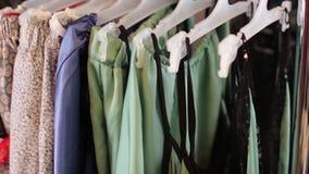 Женские руки исправили одежды на вешалках в нижнем белье магазина акции видеоматериалы