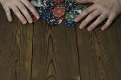 Женские руки и обломоки покера на деревянном стоге предпосылки стоковая фотография rf