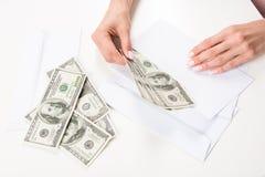 Женские руки кладя банкноты доллара в конверт Стоковое Изображение RF