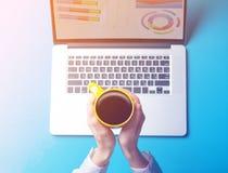 Женские руки коммерсантки с компьтер-книжкой и чашкой кофе Стоковая Фотография