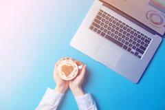 Женские руки коммерсантки с компьтер-книжкой и чашкой кофе Стоковое Фото