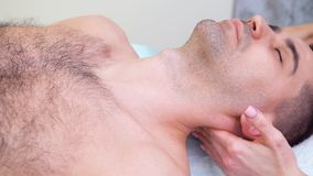 Женские руки массажируя плечи и шею мужского пациента в комнате терапией сток-видео
