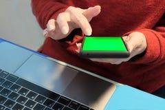 Женские руки на смартфоне Шаблон для врезать любое изображение на экране мобильного телефона Зеленый ключ chroma Работа в офисе стоковое изображение