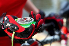 Женские руки нося перчатки велосипеда держат компас Стоковые Фотографии RF