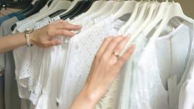 Женские руки, одежды на шкафе акции видеоматериалы