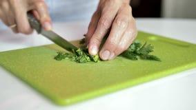 Женские руки отрезали зеленые цвета с ножом металла на яркой ой-зелен разделочной доске, конце-вверх сток-видео