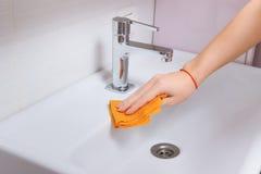 Женские руки очищая кран с оранжевой тканью Весна очищает вверх Стоковые Фото
