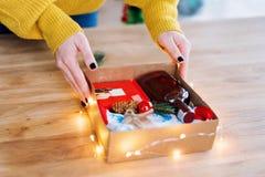 Женские руки пакуя подарок на рождество на деревянном столе Оборачивающ подарки дома Стоковое Изображение