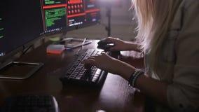 Женские руки печатая состав команд вычислительной машины, рубя компьютер на темной комнате Хакер, программист на работе акции видеоматериалы