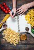 Женские руки писать блокнот специи, макаронные изделия и овощи вокруг тетради на деревянном столе Модель-макет Стоковое фото RF