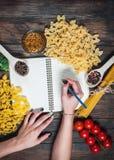 Женские руки писать блокнот специи, макаронные изделия и овощи вокруг тетради на деревянном столе Модель-макет Стоковые Изображения RF