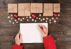 Женские руки писать список подарка рождества на бумаге на деревянной предпосылке с подарками и ярлыками стоковое изображение rf