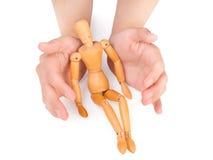 Женские руки покрывая деревянного человека Стоковое Изображение