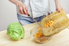 Женские руки прерывают свежую морковь для салата на борту Стоковые Изображения RF
