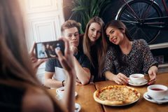 Женские руки принимая фото с smartphone молодых жизнерадостных друзей стоковое изображение