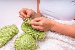 Женские руки при иглы вязать с зелеными шерстями Стоковое Изображение