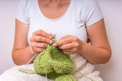 Женские руки при иглы вязать с зелеными шерстями Стоковые Изображения