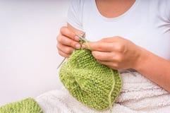 Женские руки при иглы вязать с зелеными шерстями Стоковые Изображения RF