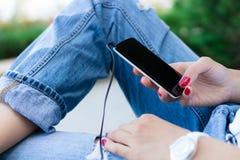 Женские руки при красный маникюр держа мобильный телефон с h стоковое изображение rf