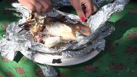 Женские руки развертывают свежих рыб испеченных в фольге в внешних тлеющих углях камина 4K видеоматериал