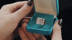 Женские руки раскрывают голубую шкатулку для драгоценностей бархата, принимают вне кольцо с бриллиантом сток-видео