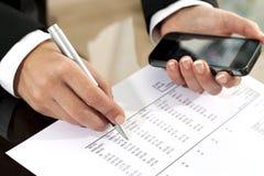 Женские руки рассматривая документ бухгалтерии. Стоковые Изображения