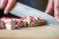 Женские руки режа плодоовощ клубники и нугу гайки с ножом на деревянной доске Стоковая Фотография