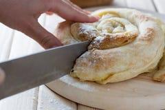 Женские руки режа свеже испеченный пирог сыра Стоковое Фото