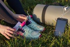 Женские руки связывая идущие ботинки и подготавливают для тренировки на предпосылке циновки йоги, и телефоне с наушниками, конце- стоковая фотография rf