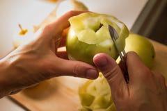 Женские руки слезая кожу зеленого яблока используя обстрагивая нож Стоковое Изображение RF