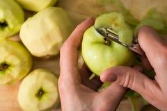Женские руки слезая кожу зеленого яблока используя обстрагивая нож Стоковое Изображение